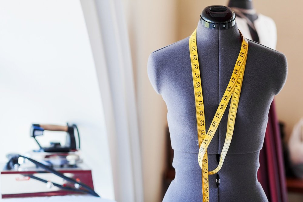 Black dummy with measuring tape in tailors studio